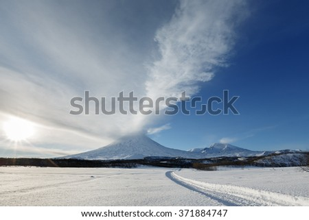 Volcanic landscape of Kamchatka Peninsula: wintry view of eruption active Klyuchevskaya Sopka (Klyuchevskoy Volcano) - ejection from crater of volcano plume of gas, steam, ashes. Far East, Russia. - stock photo