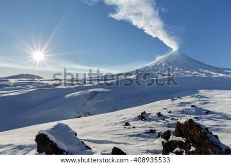 Volcanic landscape of Kamchatka: winter view of eruption active Klyuchevskaya Sopka (Klyuchevskoy Volcano) - emission from crater plume of gas, steam and ashes. Klyuchevskaya Group of Volcanoes. - stock photo