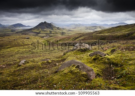 Volcanic landscape with rocks and dramatic cloudy sky in Iceland - stock photo