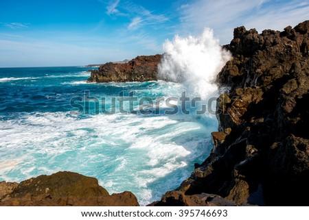 Volcanic Los Hervideros coastline with wavy ocean and blue sky on Lanzarote island in Spain - stock photo