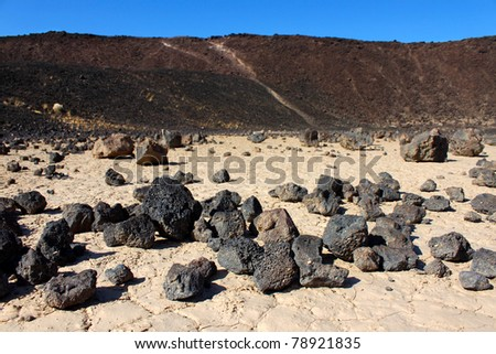 Volcanic rock scatters the center of Amboy Crater in the deserts of southern California - stock photo