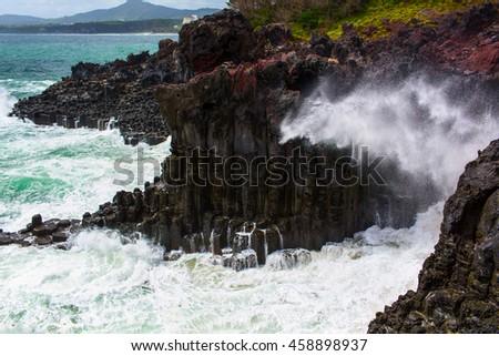 Volcanic rocky coast with storming sea - stock photo
