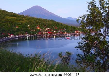 Volcano Agung (Bali island, Indonesia) lighted by rising sun and calm lagoon with sail boat - stock photo