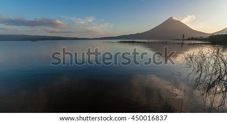 Volcano Arenal in Costa Rica at dawn with reflection in the water - stock photo