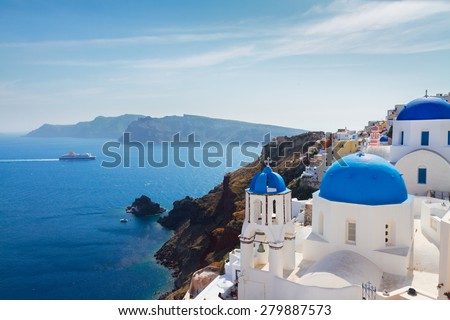 volcano caldera with blue church domes at sunny day, Oia, Santorini - stock photo