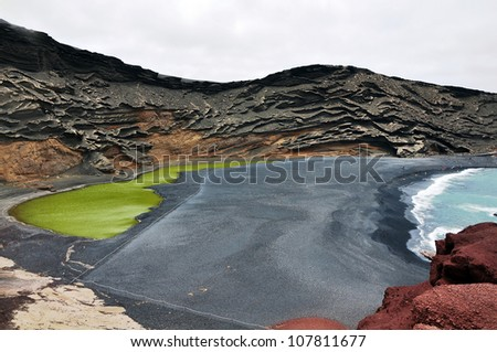 Volcano crater as black sand beach on Lanzarote - stock photo