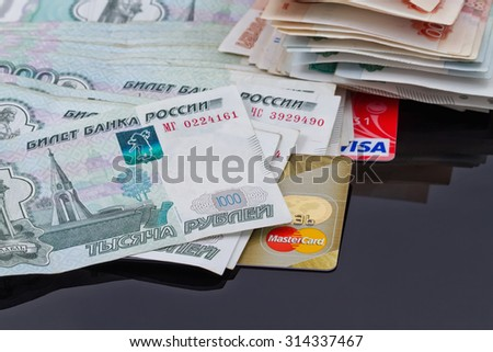 VOLGOGRAD - AUGUST 16: Plastic card payment systems Visa and MasterCard are with a bunch of Russian money . August 16, 2015 in Volgograd, Russia. - stock photo