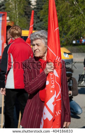 VOLGOGRAD, RUSSIA - MAY 1, 2011:Woman with flag takes part in the May day demonstration in Volgograd - stock photo