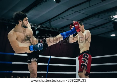 Volgograd, Russia - October 24, 2015: MMA athlete gets a kick in head of opponent during Championship of Russia on mixed martial arts - stock photo