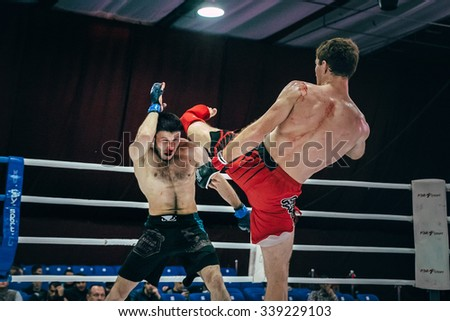 Volgograd, Russia - October 24, 2015: MMA fighter strikes hand on head of an opponent lying on floor ring during Championship of Russia on mixed martial arts - stock photo