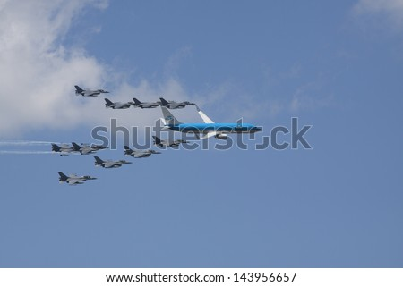 VOLKEL, NETHERLANDS - JUN 15: A Boeing 737 escorted by 10 fighter jets during the Royal Netherlands Air Force Day on June 15, 2013 in Volkel, Netherlands. - stock photo