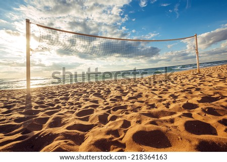 Volleyball net and sunrise on the beach  - stock photo