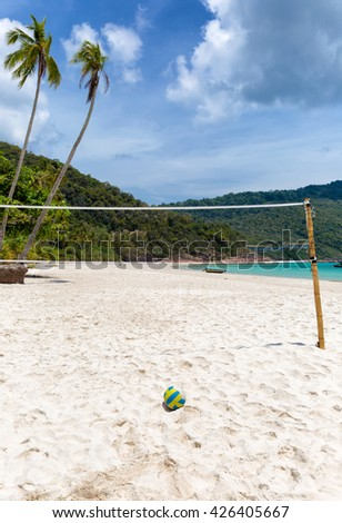 Volleyball net and volleyball laying in the sand on a tropical beach - stock photo