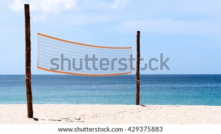 Volleyball net on beach with blue sea, clear and sunny sky. - stock photo