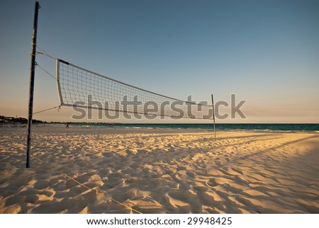 Volleyball net on tropical beach - stock photo