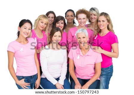 Voluntary cheerful women posing and wearing pink for breast cancer on white background - stock photo