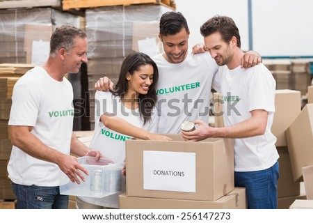 Volunteer team packing a food donation box in a large warehouse - stock photo