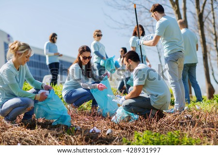 volunteering, charity, cleaning, people and ecology concept - group of happy volunteers with garbage bags cleaning area in park - stock photo