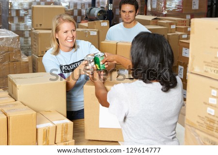 Volunteers Collecting Food Donations In Warehouse - stock photo