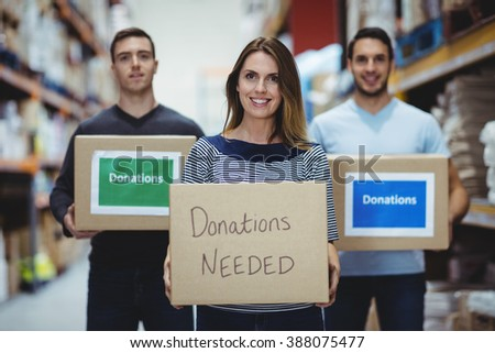 Volunteers smiling at camera holding donations boxes in a large warehouse - stock photo