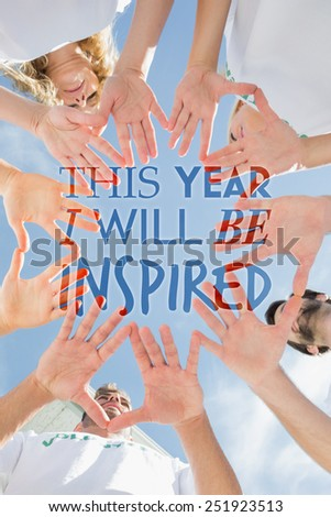 Volunteers with hands together against blue sky against i will be inspired - stock photo