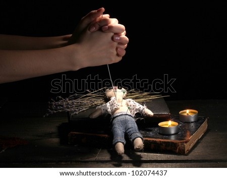 Voodoo doll boy pierced by a needle on a wooden table in the candlelight - stock photo