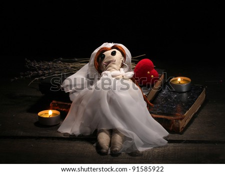 Voodoo doll girl-bride on a wooden table in the candlelight - stock photo