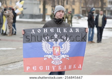 "VORONEZH, RUSSIA - MARCH 1: Unidentified pro-Putin provoker holds flag of  ""DNR""(Donetsk People Republic) at the rally dedicated to Boris Nemtsov murder on March 1, 2015, Voronezh, Russia. - stock photo"