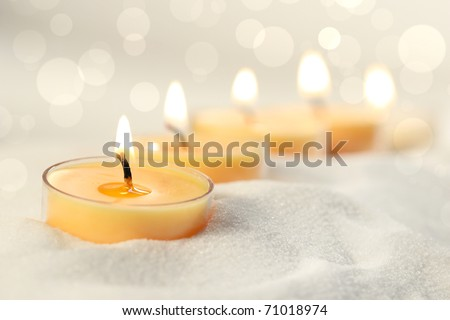 Votive candles in sand lit and arranged for ambiance - stock photo