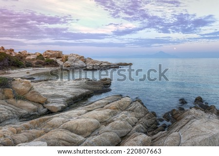 Vourvourou - Karidi beach with mount Athos in the background surprised at sunset. - stock photo