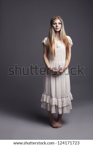 vulnerable barefooted childish girl standing and looking at camera unconfidently - stock photo