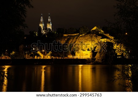Vysehrad with Basilica of St Peter and St Paul in Prague from Vltava river side, Vysehrad, Czech Republic. Famous tourist destination beatifully lighted in the night. - stock photo