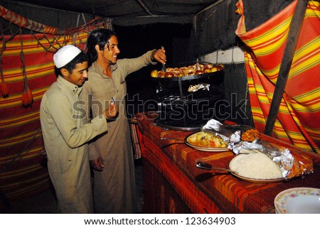 WADI RUM, JORDAN - NOV 10 2007:Arab men cook Arab food in Wadi Rum,Jordan.It's a traditional dish of the Arab Levant of meat, rice and fried vegetables in a pot that flipped upside down when served - stock photo