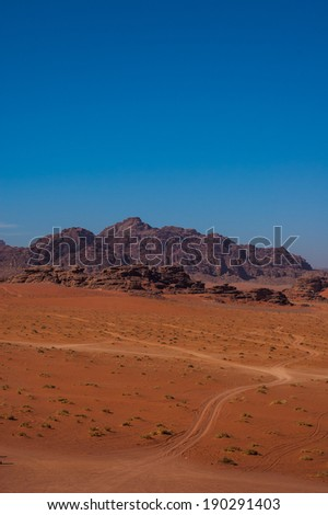 Wadi Rum,? The Valley of the Moon , Mountain Scenic View With Blue Sky and a Sand Path. Dramatic view of the Desert. Jordan Tourism. - stock photo