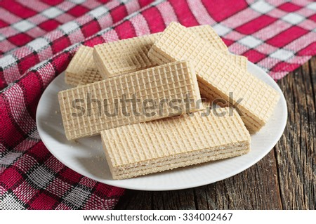 Wafers in plate on dark wooden table with red tablecloth   - stock photo