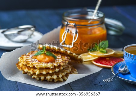 Wafers on baking paper, a jar of persimmon jam with spoon, blue cup of tea, slices of lemon and grapefruit, saucer with a small sieve on blue dark rustic background. Horizontal view. Focus on wafers. - stock photo