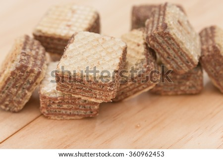 Wafers with chocolate on wooden background. - stock photo