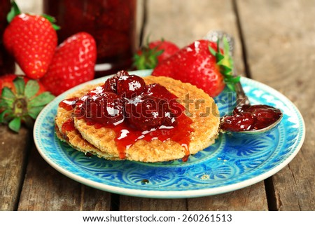 Wafers with strawberry jam and berries on plate on table close up - stock photo