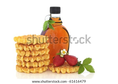 Waffle stack and maple syrup with strawberry fruit and flower blossom with leaf sprig,  isolated over white background with copy space. - stock photo
