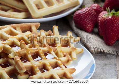Waffles covered with maple syrup - stock photo