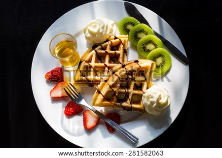 waffles with chocolate sauce, ice cream and strawberries  - stock photo