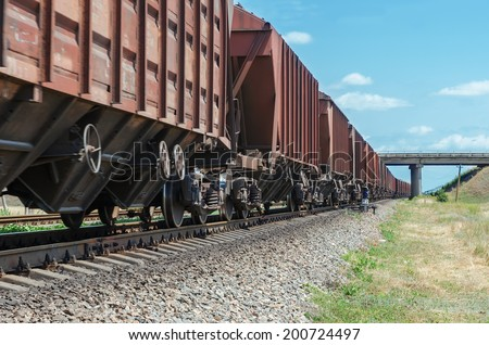 wagons of a freight train in motion go to horizon under bridge - stock photo