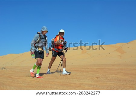 WAHIBA DESERT, OMAN - JANUARY 29: Two unidentified runners running in desert, on January 29, 2014. Desert running is part of the extreme endurance marathon Transomania. - stock photo