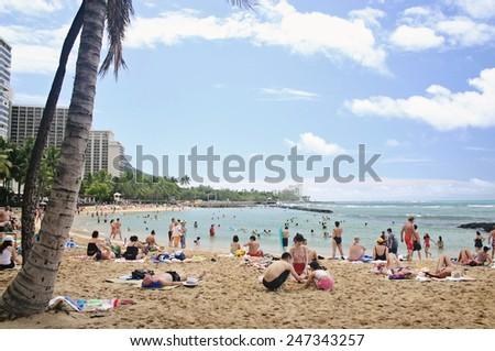 WAIKIKI, HAWAII - MAR 7: Tourists sunbathing and surfing on Waikiki beach in Honolulu, Hawaii on March 7 2006. Waikiki white sand beach shoreline is Hawaii's most famous beach .  - stock photo