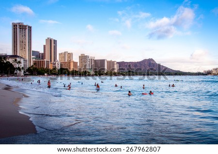 WAIKIKI, HI- JUNE 25 - Waves crashing on famous Waikiki beach in Honolulu Hawaii on June 25, 2013 in Waikiki, Hawaii. Picture is taken at sunset, but many tourists are still swimming. - stock photo