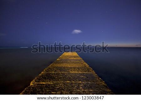 Waikiki Honolulu Hawaii jetty with star filled night sky. - stock photo
