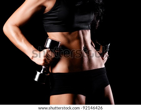 waist and hands of a beautiful sporty muscular woman working out with two dumbbells, isolated against black background (focus on the belly) - stock photo