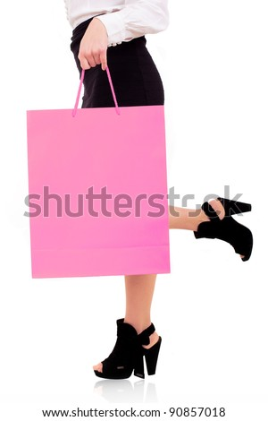 waist-down view of woman carrying a pink shopping bag - stock photo