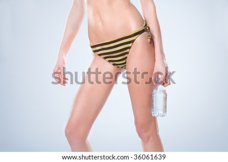 Waist-down view of woman standing in a swimsuit and holding a water bottle - stock photo