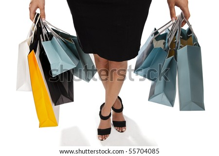 Waist-down view of young woman carrying shopping bags - stock photo